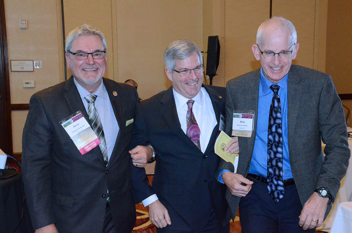 Newly elected President R. James Valentine being escorted to the podium by past Presidents Richard Thirlby and Gregory Jurkovich.